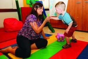 Woman helping a boy in the classroom occupational therapy